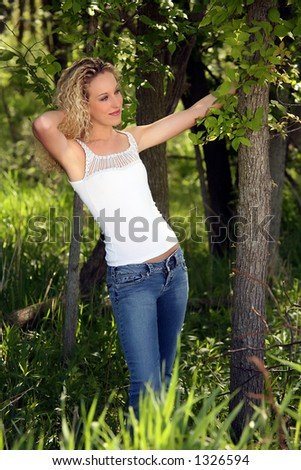 Pretty young blonde woman in blue jeans and white tank top