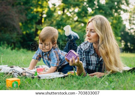 Pretty young blonde woman in checkered shirt having fun in park with cute little son. Handsome mother with baby boy outdoors
