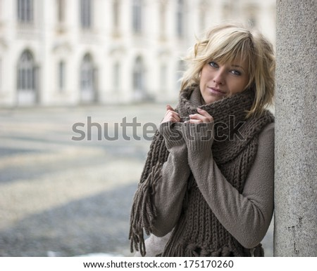 Pretty young blonde woman outdoors, wearing wool scarf and sweater, leaning on marble column