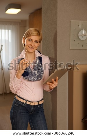 Pretty young blonde woman using tablet computer, smiling, looking at camera. - stock photo
