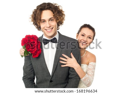 Pretty young bride posing from behind handsome groom - stock photo