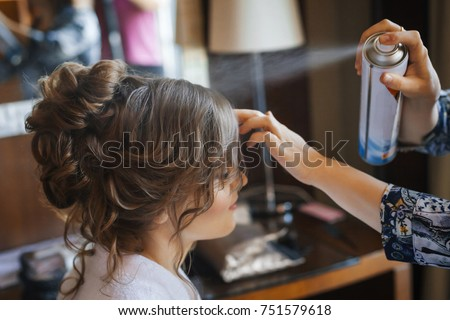 Pretty young bride preparing for wedding at home in the morning. Stylist making hairstyle and apply hairspray on curly hair