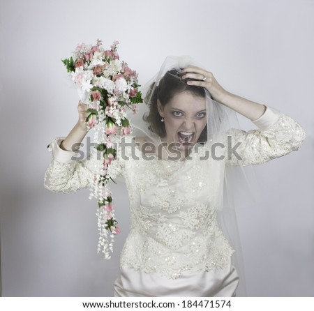 Pretty young bride screaming and holding bouquet with pink roses - stock photo