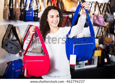 Pretty young brunette choosing bag among assortment in store