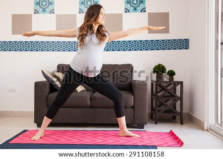 Pretty young brunette doing some yoga exercises at home during her pregnancy - stock photo