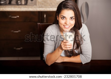 Pretty young brunette enjoying a glass of milk at home and smiling - stock photo