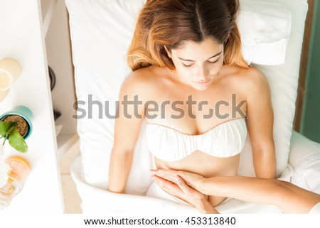 Pretty young brunette getting a lymphatic stomach massage from a therapist at a health clinic and spa, seen from above - stock photo