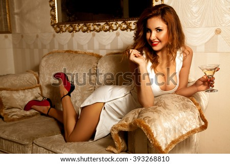 Pretty young brunette lady in sexy white dress posing with glass of martini. Seductive woman. Sexual woman. the concept of seduction, pleasure and desire - stock photo