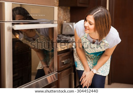Pretty young brunette looking into an oven and checking if the cake is already baked and ready - stock photo