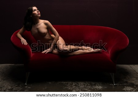 Pretty young brunette lying nude on a red couch - stock photo