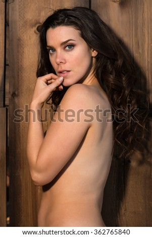 Pretty young brunette nude against a wooden door