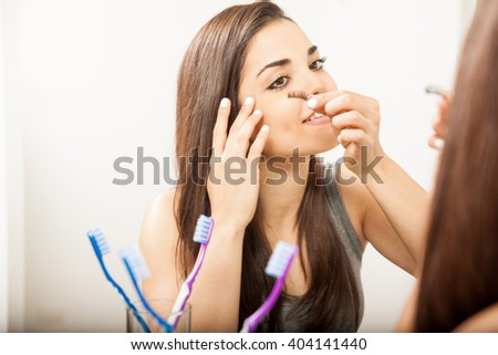 Pretty young brunette putting a false eyelash while standing in front of a mirror in a bathroom - stock photo