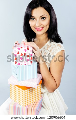 Pretty young brunette sitting with a stack of present boxes - stock photo