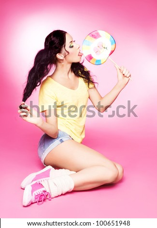 pretty young brunette woman eating a lollipop, isolated against white background