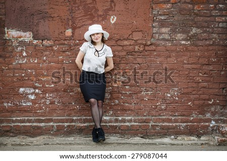 Pretty young brunette woman in a white hat, blouse and black skirt, posing outdoor in old vintage brown brick wall background. Girl is leaning against the wall. Space for text. - stock photo