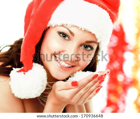 Pretty young brunette woman on santa hat with snow her hands - stock photo