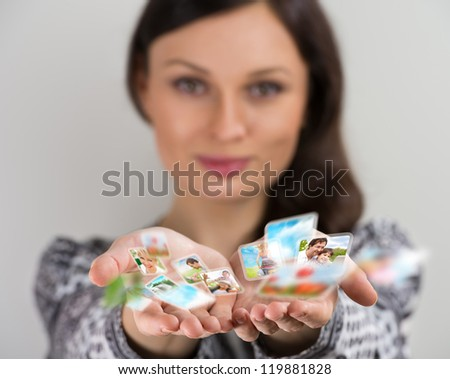 Pretty young brunette woman smiling with hands cupped together, sharing her photo and video files in social media resources. Virtual interface of future concept. - stock photo