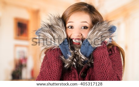 Pretty young brunette woman squeezing her head between large blue scarf and smiling, freezing cold concept. - stock photo