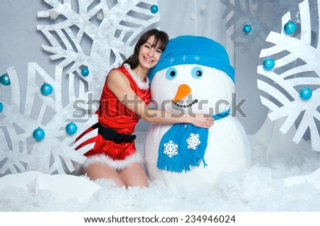 Pretty young brunette woman wearing Santa Claus costume, sitting near snowman, embracing him, smiling with toothy smile, looking at camera, in a white decorated rood with winter trees - stock photo