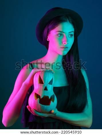 pretty young brunette woman with pumpkins. studio - stock photo