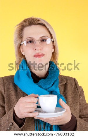 pretty young business woman drinking the coffee on the yellow background - stock photo