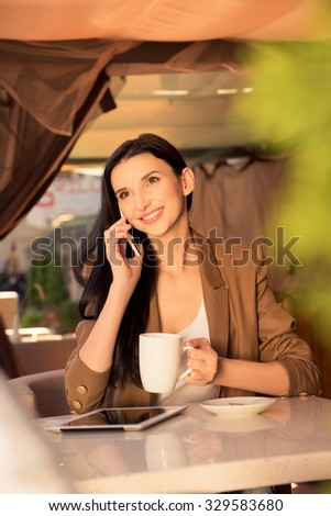 Pretty young business woman in a cafe drinking tea and talking on the phone