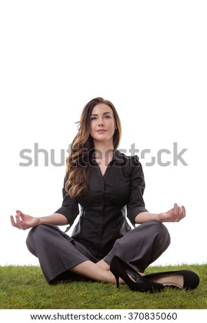 Pretty young business woman in a suit, sitting on grass in a crossed legs yoga pose, with her arms resting on her knees, palms upwards isolatd on white - stock photo