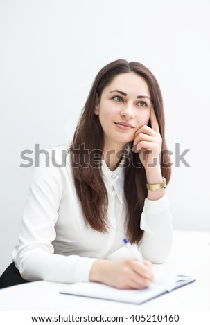 Pretty young business woman thinking about plans and writes in diary - stock photo