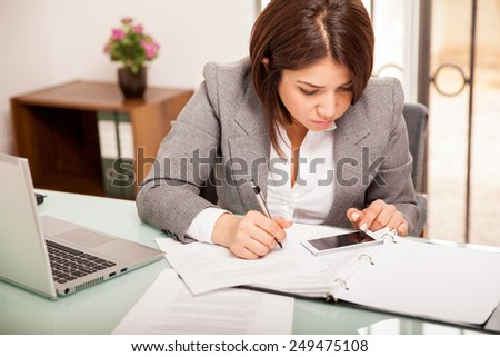 Pretty young business woman using her smart phone to work on her taxes at an office - stock photo