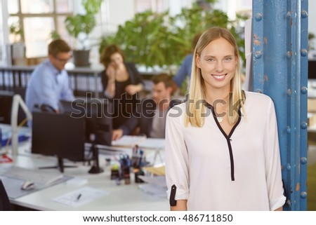 Pretty young businessman with a lovely smile standing in the foreground in an open plan office as colleagues work in the background