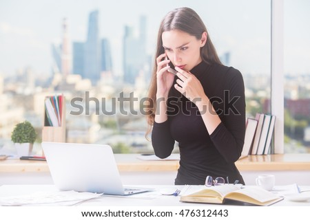 Pretty young businesswoman at office desk talking on mobile phone and using laptop computer. Blurry city view in the background