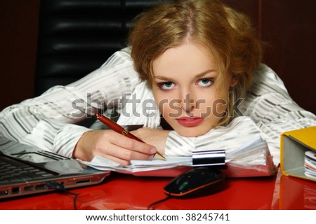 Pretty young businesswoman dressed white  at workplace signs the document - stock photo