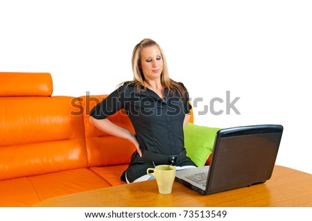 Pretty young businesswoman giving herself a back rub in front of her laptop - stock photo