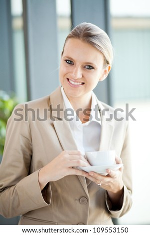 pretty young businesswoman having coffee break at work - stock photo