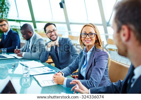Pretty young businesswoman in suit and eyeglasses looking at her colleague during talk - stock photo