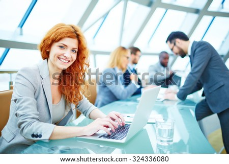 Pretty young businesswoman looking at camera while typing - stock photo