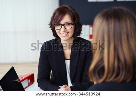 Pretty Young Businesswoman Smiling at the Camera While Talking with her Co-worker During a One-on-One Meeting inside the Office. - stock photo