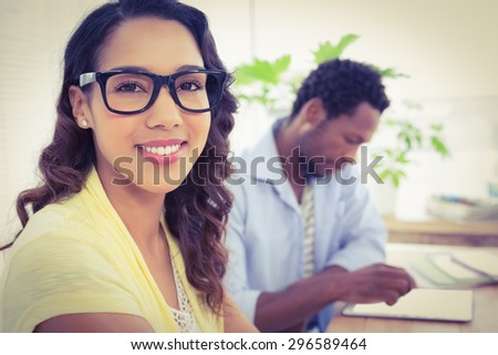 Pretty young businesswoman smiling at the camera with a businessman behind her in the office. - stock photo