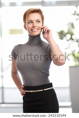 Pretty young businesswoman talking on mobilephone at office building. - stock photo