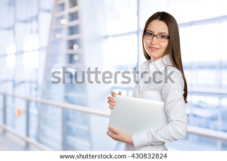Pretty young businesswoman with laptop - stock photo