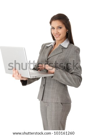 Pretty young businesswoman working on laptop, smiling at camera. - stock photo