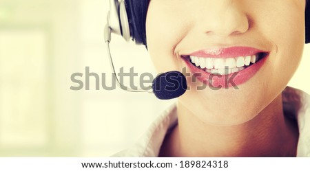 Pretty young call center worker wearing a headset - stock photo