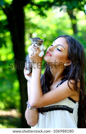 Pretty young caucasian girl with cute little kitten in the park