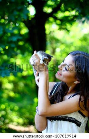 Pretty young caucasian girl with kitten on her hands