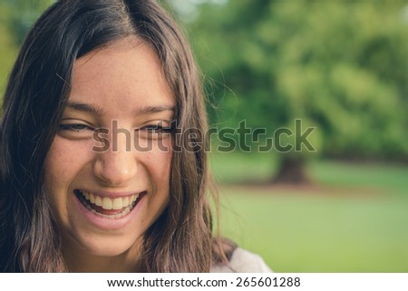 Pretty young caucasian woman laughing cheerfully. Green natural environment in background. Filtered effects. With copy space.