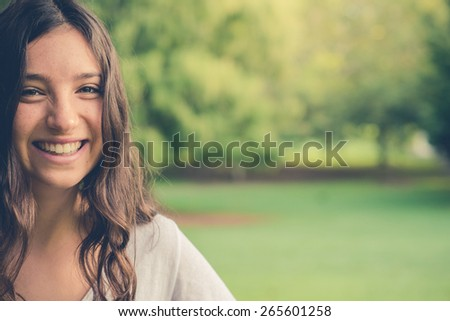 Pretty young caucasian woman smiling cheerfully looking at camera. Green natural environment in background. Filtered effects. With copy space. - stock photo