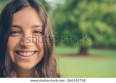 Pretty young caucasian woman smiling cheerfully looking at camera. Green natural environment in background. Filtered effects. With copy space.