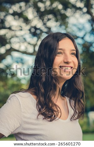 Pretty young caucasian woman smiling cheerfully looking away. Green natural environment in background. Filtered effects