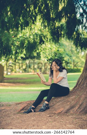 Pretty young caucasian woman wearing black jeans sitting outside under a tree reading a book. Filtered effects - stock photo