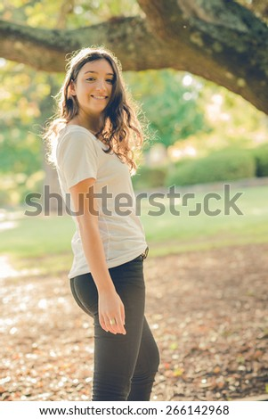 Pretty young caucasian woman wearing black jeans walking outside in a park and turning to look back. Filtered effects - stock photo